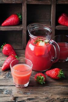 Słodki pyszny sok truskawkowy na drewnianym stole, selektywne focus