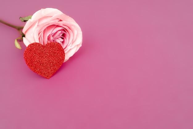 Słodki różowy kwiat róży dla miłości romantyczne tło z sercem. miękka selektywna ostrość. skopiuj miejsce.
