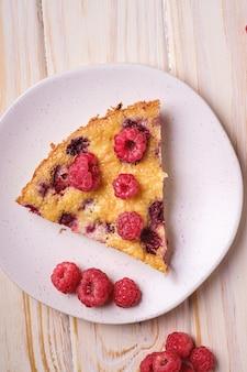 Słodki smaczny kawałek ciasta z galaretowatymi i świeżymi owocami malin w talerzu, drewniana powierzchnia stołu, widok z góry