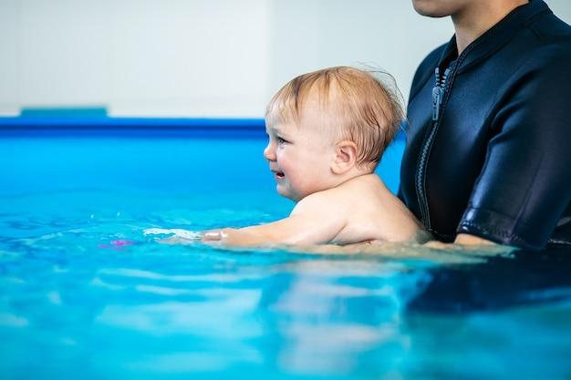 Słodki smutny chłopiec uczy się pływać w specjalnym basenie dla małych dzieci