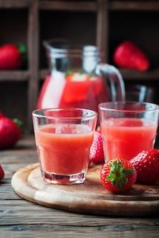 Słodki sok truskawkowy na drewnianym stole, selektywna ostrość