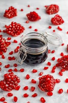 Słodki sos granatowy lub syrop do mięsa i ryb o nazwie narsharab, w szklanym słoju z oczyszczonym granatem, selektywne focus