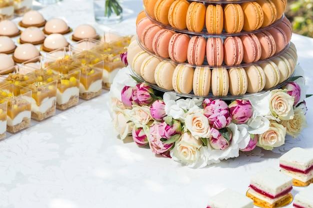 Słodki stół na bankiet z ciastami i kwiatami