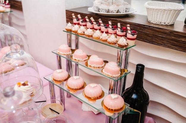 Słodki stół. talerze ciast i babeczek ze śmietaną. stół ze słodyczami, słodyczami, bufetem. stół deserowy na gadżety imprezowe na wesele. ścieśniać. batonik. urządzone pyszne.