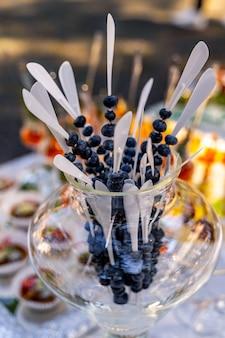 Słodki stół z jagodami. catering weselny. bar owocowy na imprezie. szkło z białymi patyczkami i jagodami na nim. zbliżenie.