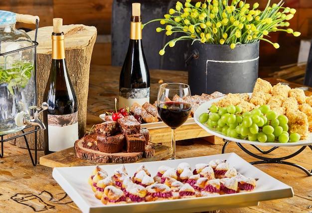 Słodki stół z wyborem ciast i ciastek z winogronami i czerwonym winem