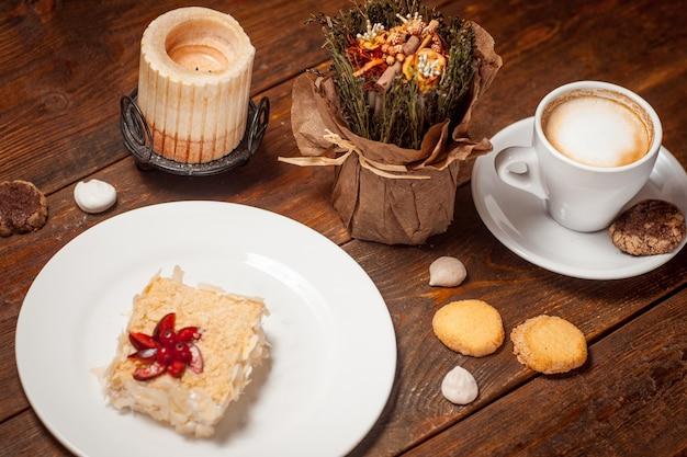 Słodki tort filiżanka kawy na drewnianym świątecznym stole
