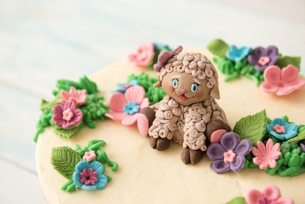 Słodki tort urodzinowy ozdobiony kwiatami i cukrowymi owcami