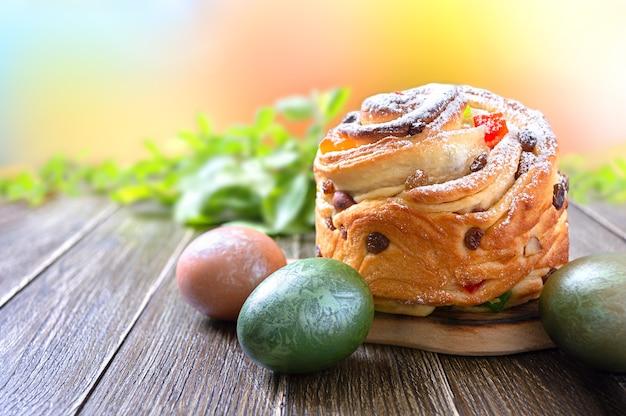 Słodki tort wielkanocny, pisanki, zielone gałązki na drewnianym stole.