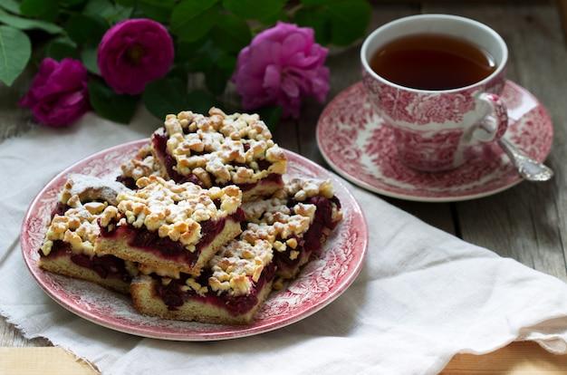 Słodki tort z aren wiśni różanymi i streusel na drewnianym tle. styl rustykalny.