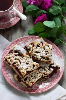 Słodki tort z arenami wiśniowo-różanymi i kruszonką na drewnianym. styl rustykalny.
