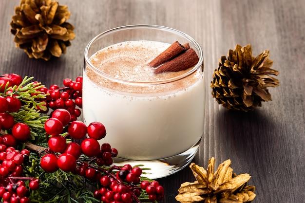 Słodki tradycyjny napój na boże narodzenie i zimę na stole z czerwonymi dekoracjami i złotą szyszką sosnową