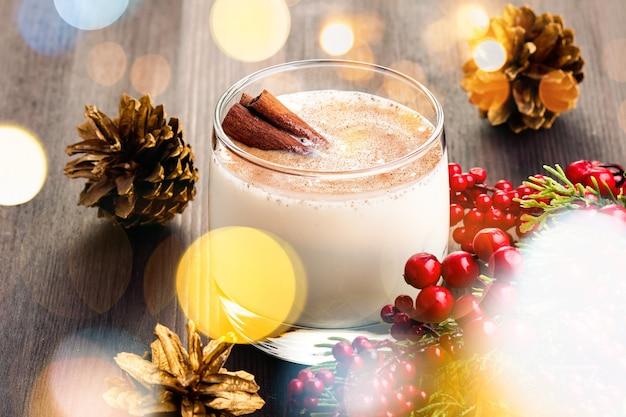 Słodki tradycyjny napój na boże narodzenie i zimę na stole z czerwonymi dekoracjami i złotymi szyszkami