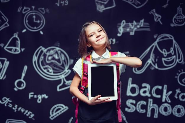 Słodki uczeń przygotowuje się do pójścia do szkoły z plecakiem pokazującym tablet z powrotem do koncepcji szkoły