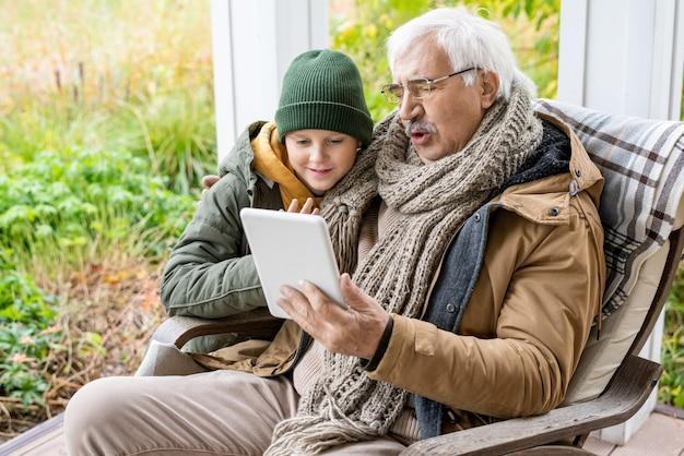 Słodki uczeń w czapce i ciepłej kurtce oraz jego dziadek z cyfrowym tabletem patrzący na ekran dotykowy podczas omawiania wiadomości na świeżym powietrzu