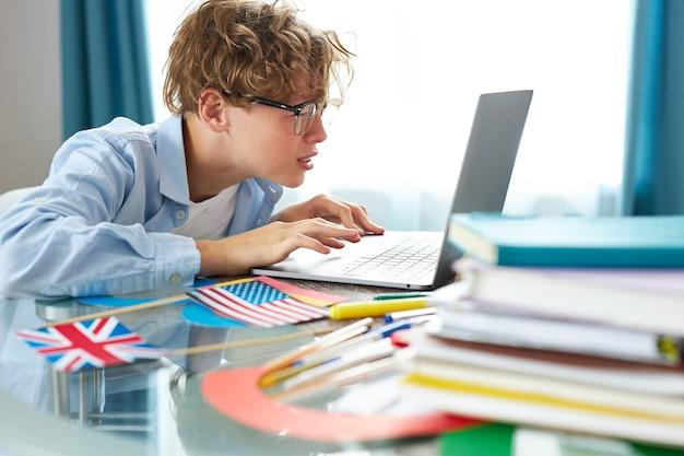 Słodki uczeń wita się przed kamerą podczas lekcji online w domu