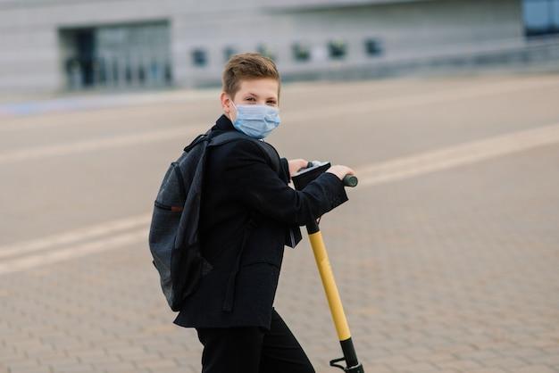 Słodki uczeń z maską ochronną prowadzący skuter w mieście.