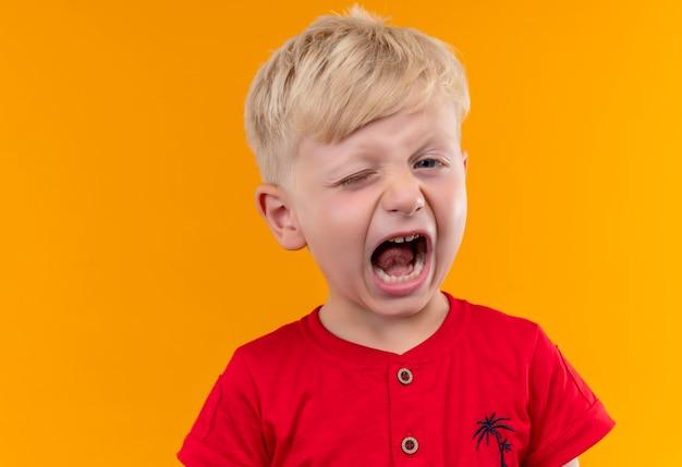 Słodki, uroczy mały chłopiec o blond włosach i niebieskich oczach ubrany w czerwoną koszulkę, patrząc z otwartymi ustami