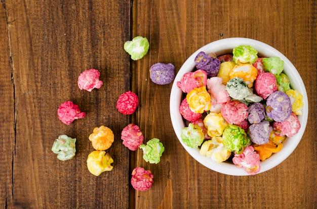 Słodki wielokolorowy karmelowy popcorn w białej kokardce