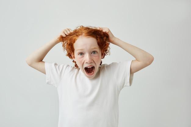 Słodki zaskoczony mały chłopiec z piegami, z szalonym wyrazem twarzy i otwartymi ustami, trzymający włosy rękami.