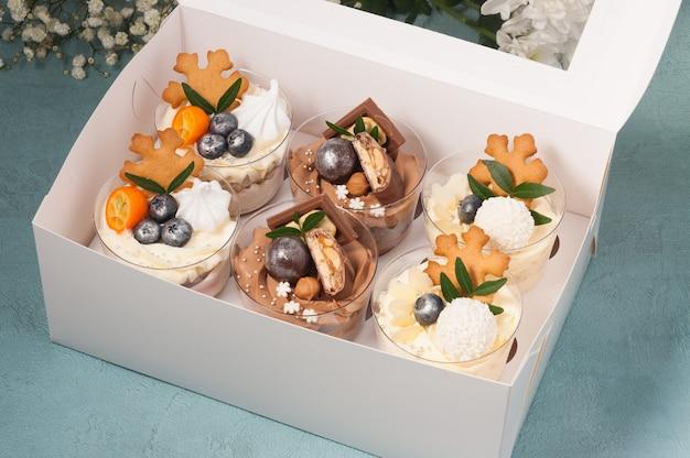 Słodki zestaw deserów w plastikowych kubeczkach ozdobionych czekoladą i owocami