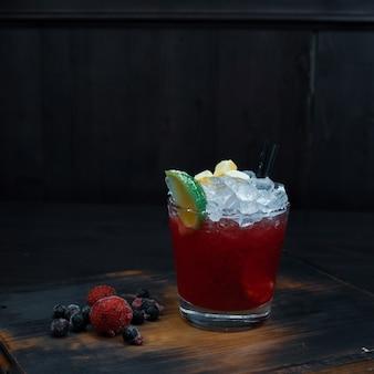 Słodki zimny koktajl alkoholowy w kolorze czerwonym ze świeżymi jagodami i plasterkami limonki stoi na drewnianym stole w pubie. koktajl podawany na zimno. oryginalne napoje serwujące. zbliżenie.