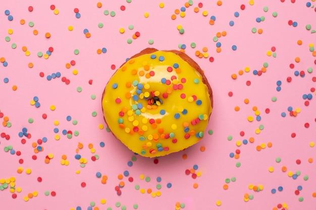 Słodki żółty pączek z posypką na różowym tle płasko leżał