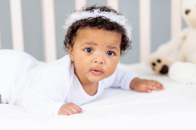Słodkie afro-amerykańskie małe dziecko leżące w łóżku do spania z opaską anioła.