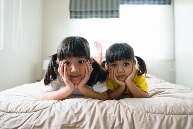 Słodkie azjatyckie dzieci leżące na łóżku