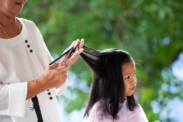 Słodkie azjatyckie dziecko dziewczyna dostaje strzyżenie przez babcię w domu