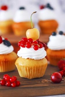 Słodkie babeczki waniliowe z nadzieniem z konfiturą jagodową i kremem serowym, ozdobione letnimi jagodami