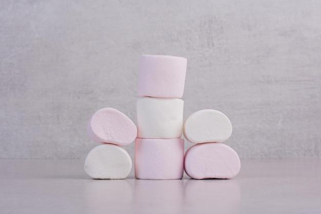Słodkie białe pianki na białym stole.