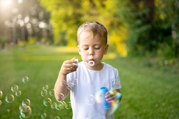 Słodkie blond dziecko nadmuchuje latem bańki mydlane na zielonym trawniku, bawiąc się, rekreacji na świeżym powietrzu