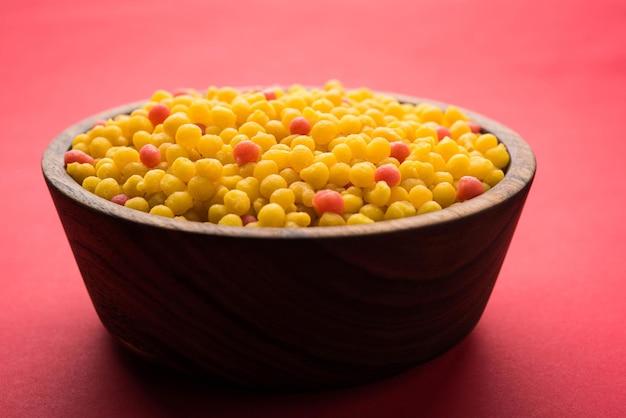 Słodkie boondi lub bundi w postaci surowej, główny składnik motichoor laddoo lub można je jeść bez zmian. indyjskie jedzenie. podawany w misce. selektywne skupienie
