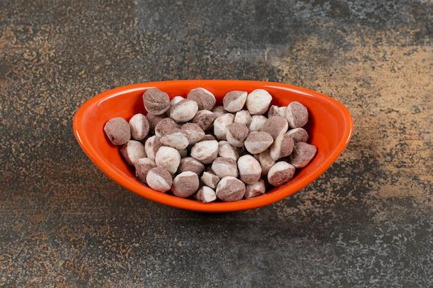 Słodkie brązowe cukierki w pomarańczowej misce.