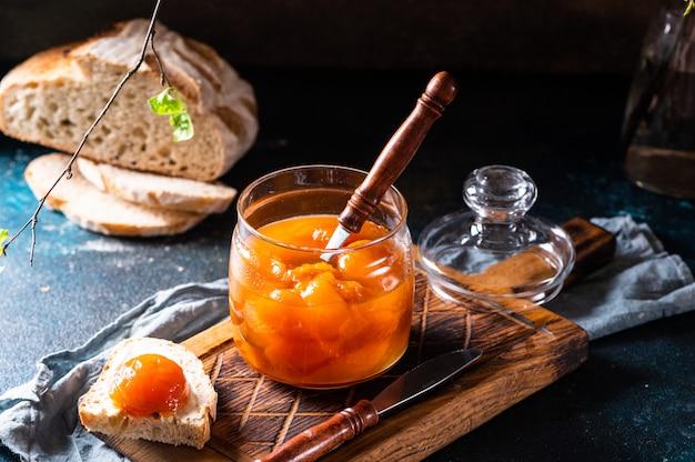 Słodkie brzoskwinie w puszkach w słoiku. dżem brzoskwiniowy. dżem domowej roboty. słodki deser. marmolada brzoskwiniowa. jedzenie wegetariańskie. koncepcja wegańskiego jedzenia. kanapka