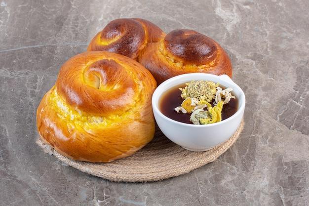 Słodkie bułeczki i filiżanka herbaty na podstawce na marmurowym tle. zdjęcie wysokiej jakości