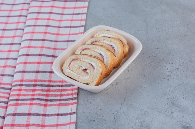 Słodkie bułki o smaku waniliowym w plasterkach na białym talerzu.