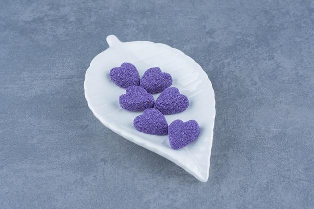 Słodkie ciasteczka na talerzu na marmurowej powierzchni