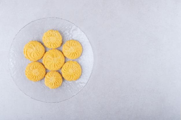 Słodkie ciasteczka na talerzu na marmurowym stole.