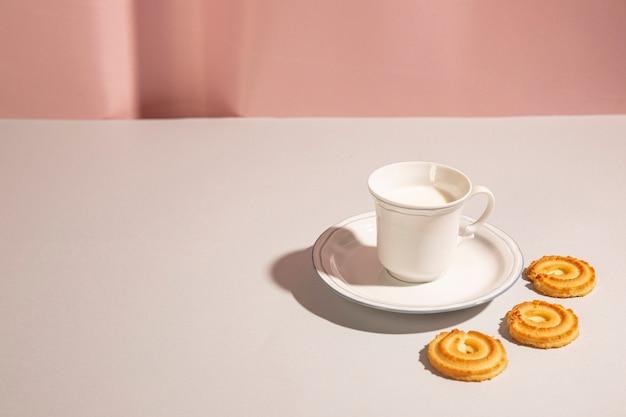 Słodkie ciasteczka ułożone wokół kubka z mlekiem na białym biurku