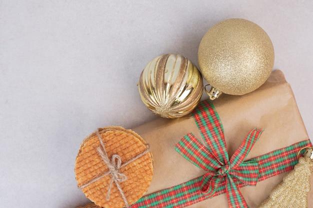 Słodkie ciasteczka w liny z prezentem i świąteczną złotą zabawką na białej powierzchni