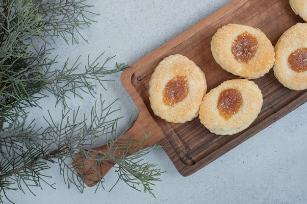 Słodkie ciasteczka z dżemem na drewnianej desce do krojenia