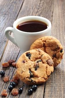 Słodkie ciasteczka z rodzynkami i jagodami i filiżankę kawy