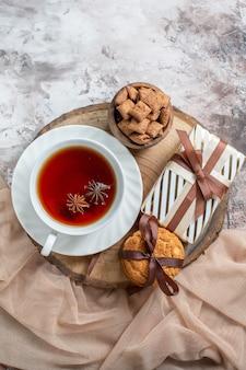 Słodkie ciasteczka z widokiem z góry z prezentem i filiżanką herbaty na podświetlanym stole