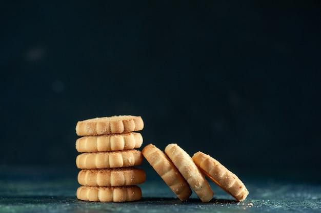 Słodkie ciasteczka z widokiem z przodu na ciemnoniebieskiej powierzchni