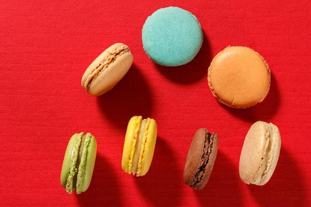 Słodkie ciastka makaroniki w innym kolorze na czerwonej powierzchni z teksturą. widok z góry