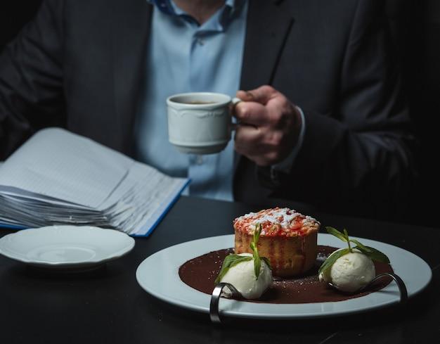 Słodkie ciastko z czarną herbatą na stole