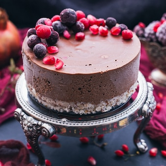 Słodkie ciasto czekoladowe z pestkami granatu i świeżymi jagodami