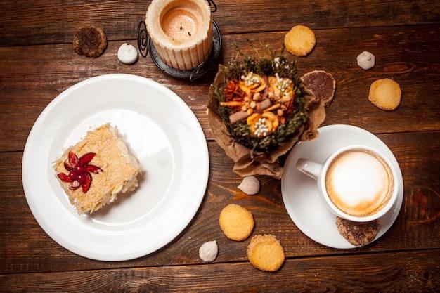 Słodkie ciasto i cappuccino na świątecznym drewnianym stole
